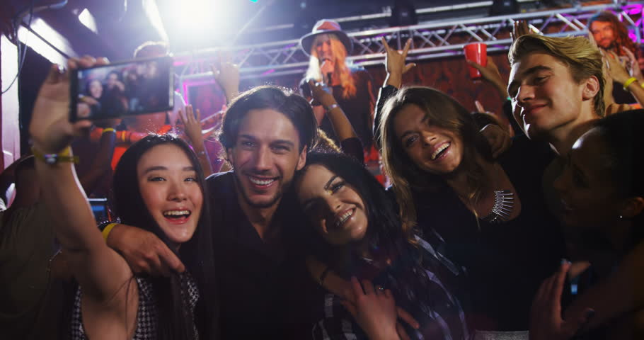 Front view of group of diverse people taking selfie with mobile phone in nightclub.