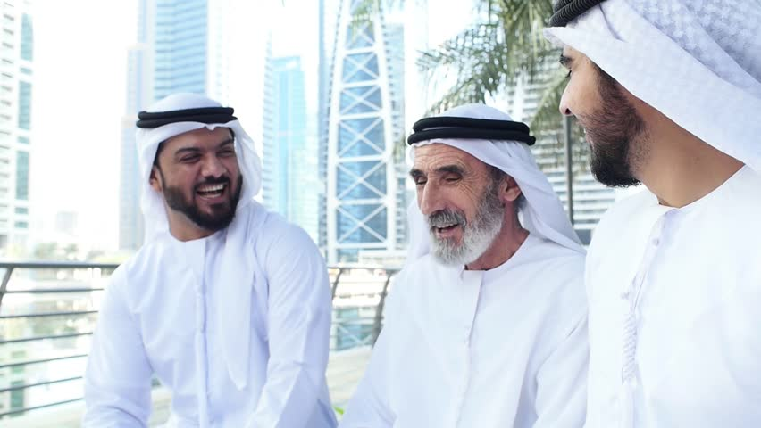 Business people working in Dubai. Senior man and two young men with kandura in uae.