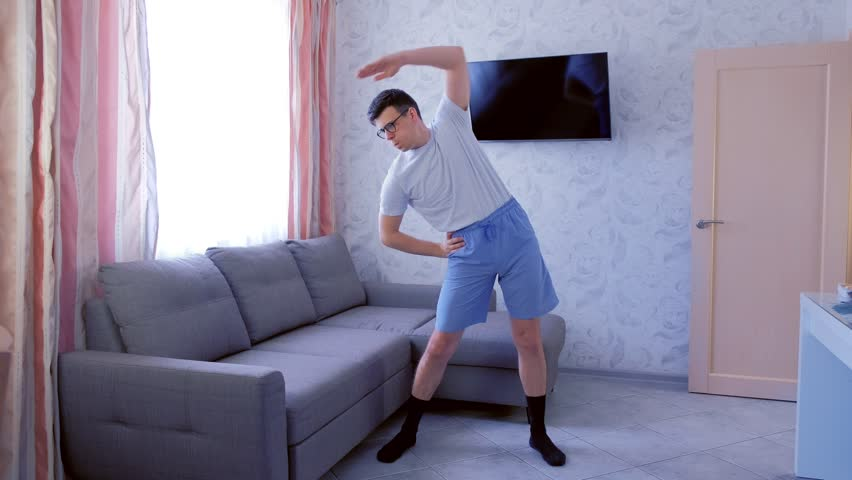 Funny nerd man in glasses and blue shorts is doing complex of fitness exercises at home. Sport humor concept. | Shutterstock HD Video #1027644749
