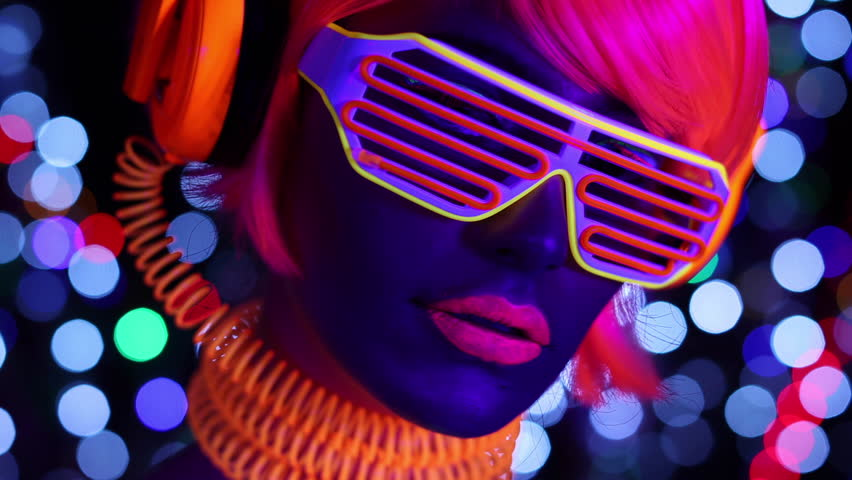 sexy cyber raver woman filmed in fluorescent clothing under UV black light