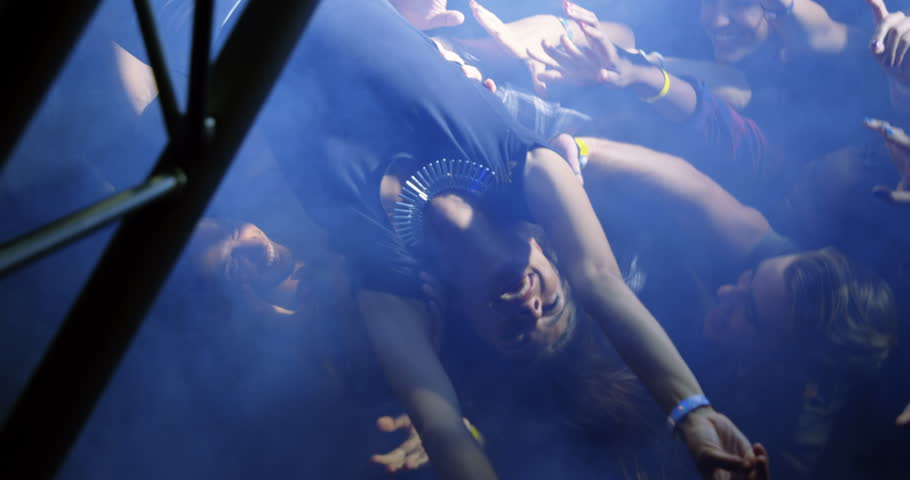Overhead view of Caucasian woman crowd surfing at a concert in nightclub.