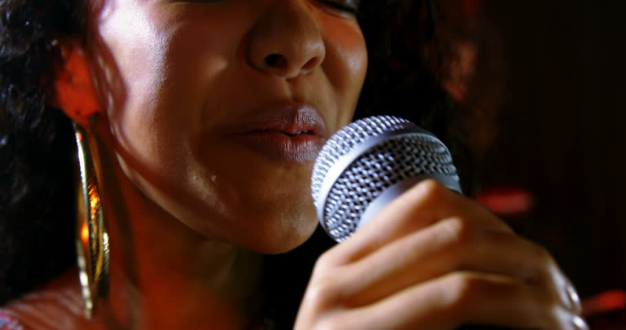 Close up of mixed race female singer performing with microphone on stage at a concert in nightclub #1027648274
