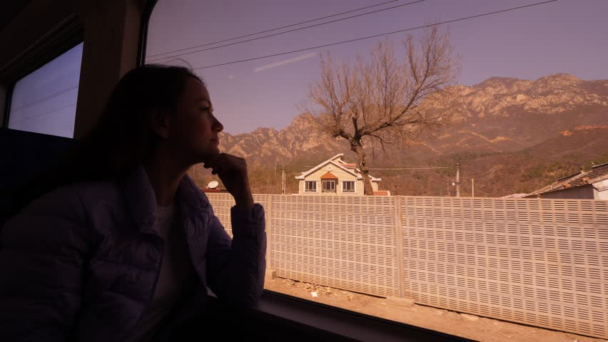 Tourist woman travel by Chinese train S2 to Badaling Great Wall, sit against window, look out. Small settlement and fence along rail track seen outdoors, mountains seen on background | Shutterstock HD Video #1027658624