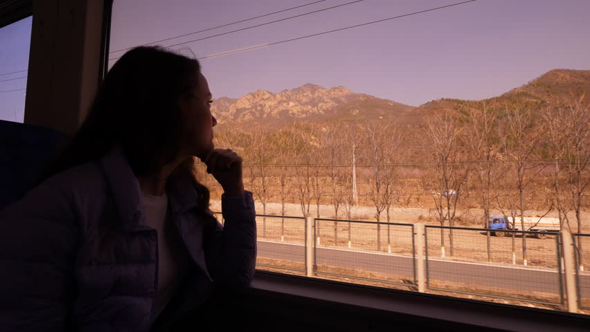 Passenger woman travel by S2 train from Beijing to Badaling, sit against window, look rural to outdoors. Mountains of Yanqing District seen on background | Shutterstock HD Video #1027658627
