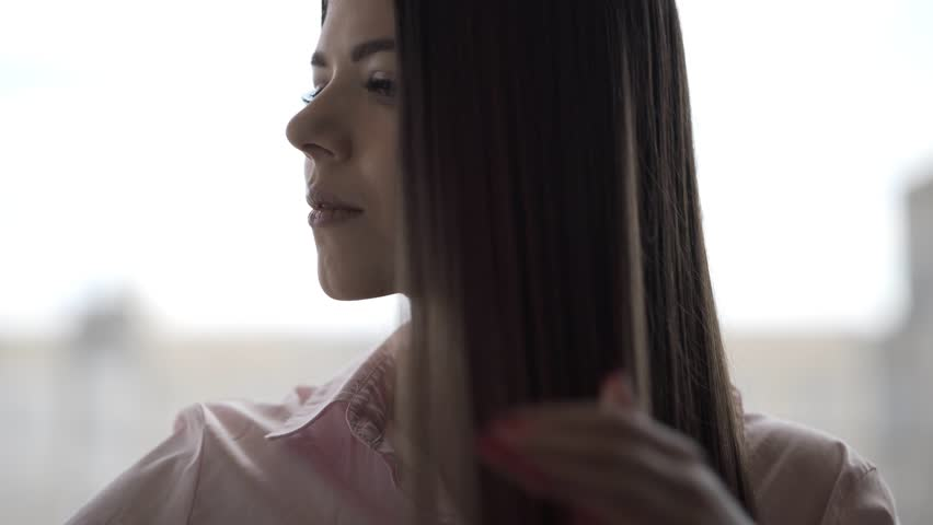 Brunette girl in a pink shirt is combing her beautiful long hair comb | Shutterstock HD Video #1027672601