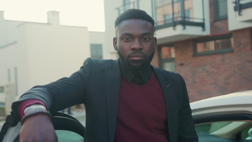 Handsome african american man stand near white car look at camera sunset young vehicle open passenger arm auto street automobile businessman buy jacket portrait close up slow motion