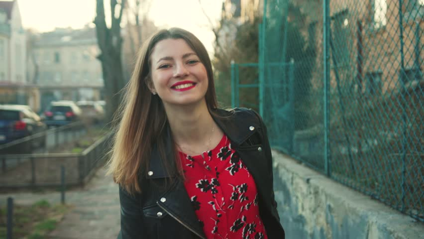 Flawless playful Caucasian girl walking through the street looking around.  Young woman looking at camera, smiling. Morning in city. Outdoors. Spring time, adult, beautiful, elegant | Shutterstock HD Video #1027674416