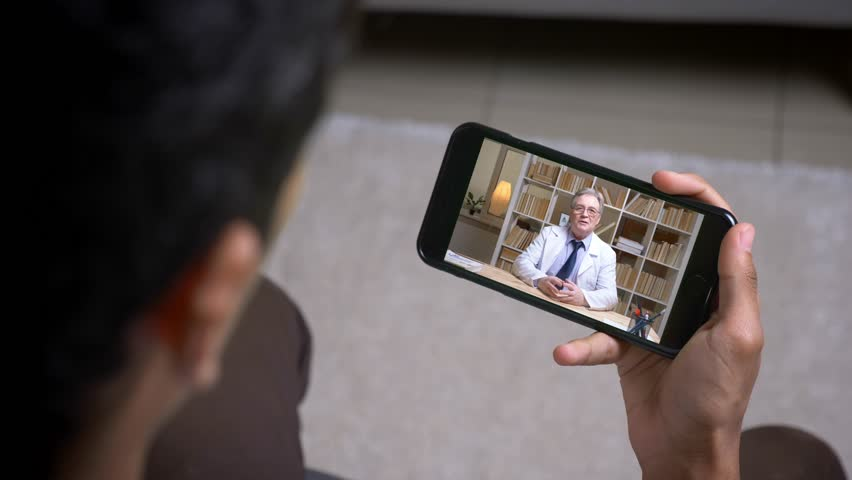 Online videocall via smartphone of senior doctor in white lab coat talking seriously to his patient behind the screen. | Shutterstock HD Video #1027689818