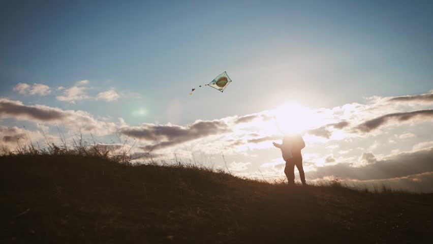 Happy family father and child daughter launch a kite on meadow at sunset. Funny family time. Concept of friendly family, travel and freedom. #1027705058