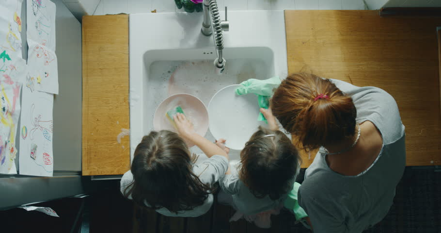 Authentic shot of little girls sisters daughters having fun to helping their mother washing plate in a kitchen on a sunny day. Royalty-Free Stock Footage #1027705577