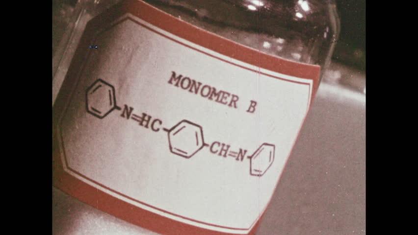 1960s: UNITED STATES: monomer B label on bottle. Monomer A label on glass jar. Man writes notes on chalk board. Formula on chalk board. | Shutterstock HD Video #1027709876