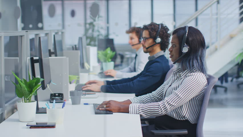 Team of Handsome and Beautiful Diverse Multicultural Customer Service Operators Working at a Busy Modern Call Center with Specialists Wearing Headsets and Actively Taking Calls.