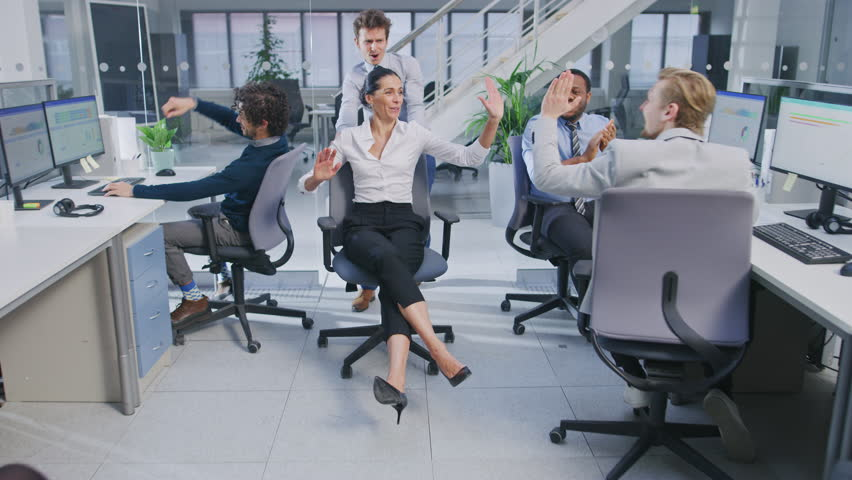 Cheerful Employee Pushes His Beautiful Female Colleague on a Chair Between Rows of Desks with Diverse Business People Working on Desktop Computers in Modern Office Space. Three High Fives Given. | Shutterstock HD Video #1027712480