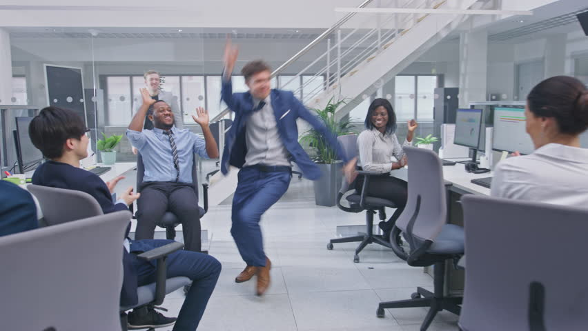 Young Happy Business Manager Wearing a Suit and Tie Dancing and Giving High Fives in the Office. Celebrating Success. Diverse and Motivated Business People Work on Computers in Modern Open Office. | Shutterstock HD Video #1027712564