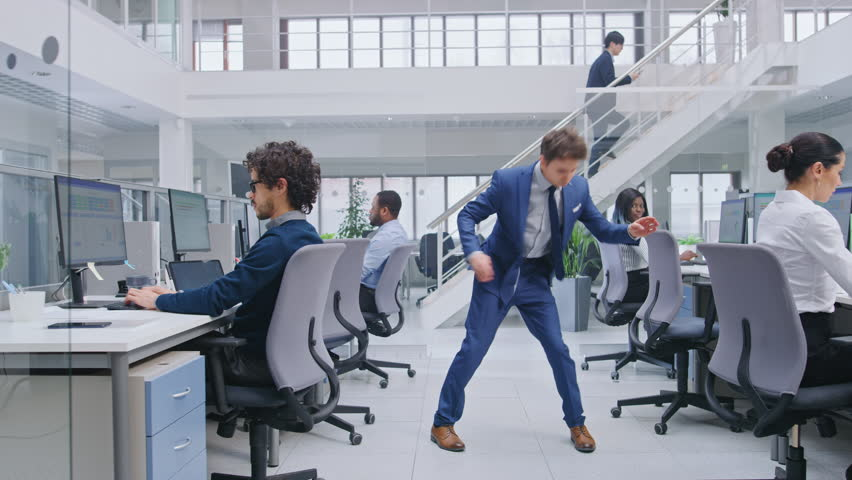Young Cheerful Handsome Business Manager Wearing a Suit and Tie Dancing in the Office. Dances Like Robot. Diverse and Motivated Business People Work on Computers in Modern Open Office. | Shutterstock HD Video #1027712570