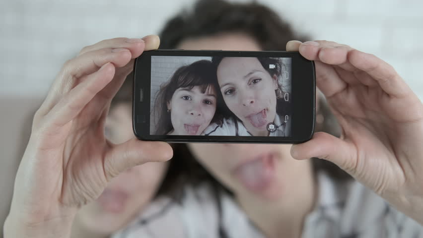 Funny selfie. A woman with a child is grimacing. Mother and daughter are photographed on a smartphone. | Shutterstock HD Video #1027728146