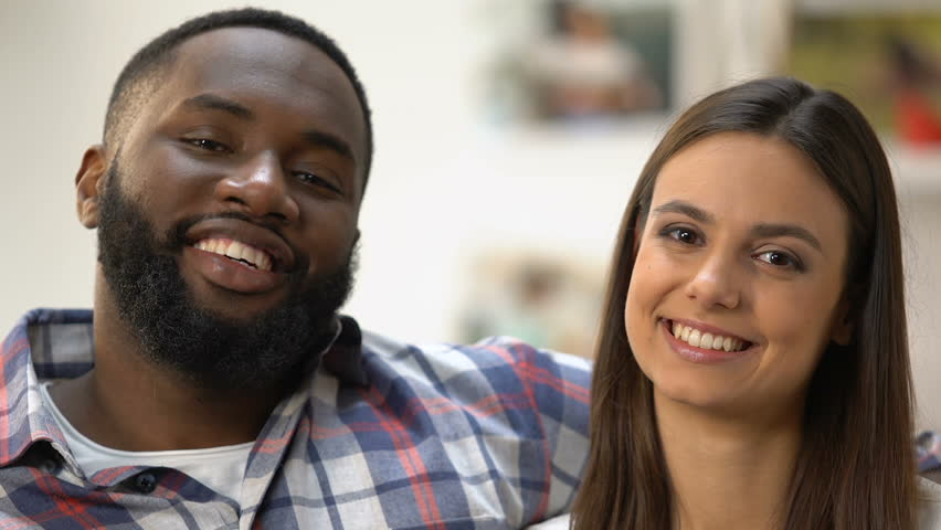 Smiling multi-ethnic couple making heart with hands, symbol of their love   Shutterstock HD Video #1027733585