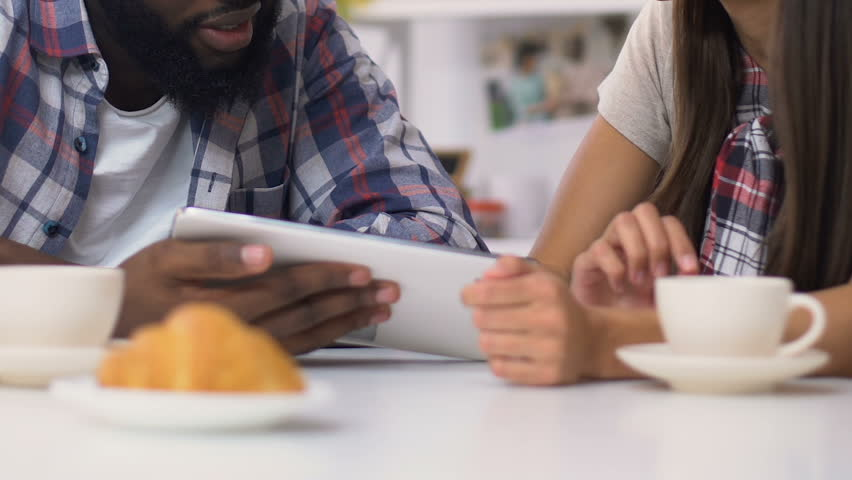 Mixed-race couple having breakfast and paying for bills on laptop, easy banking #1027733624