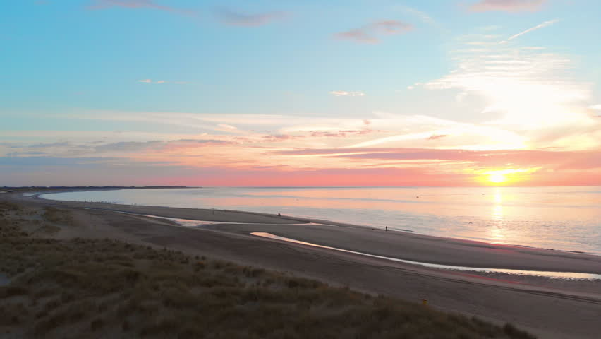A calm low tide at the beach near the Stormsurge barrier in the south west of the Netherlands, during sunset. Smooth dynamic aerial shots on the beach. Left to right, medium height. | Shutterstock HD Video #1027756751