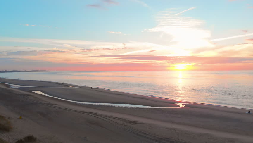 A calm low tide at the beach near the Stormsurge barrier in the south west of the Netherlands, during sunset. Smooth dynamic aerial shots on the beach. Right to left, medium height, towards the dunes. | Shutterstock HD Video #1027759934