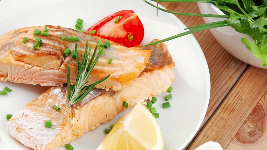 Healthy fish cuisine : grilled pink salmon steaks with red caviar in white bowl lemon and vegetable salad dish with cutlery and pepper grinder over wooden table 1920x1080 intro motion slow hidef hd | Shutterstock HD Video #10277720