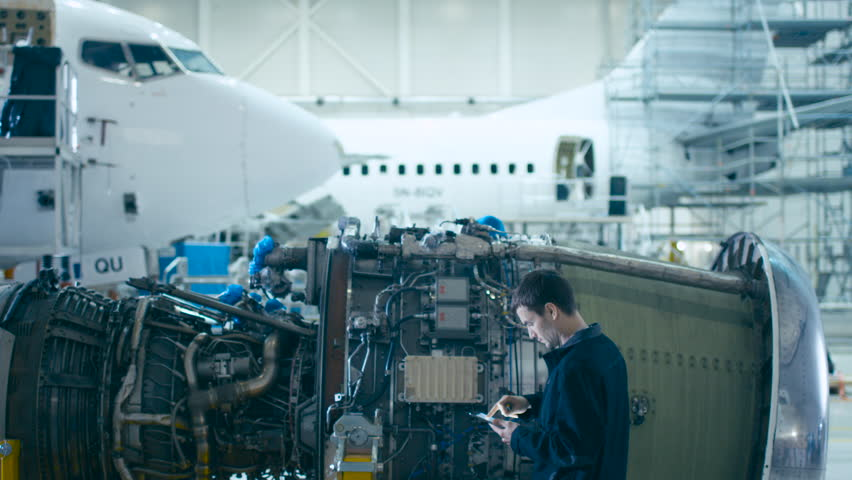 Aircraft Maintenance Mechanic Uses Digital Tablet Computer to Analyze, Inspect and Work on Airplane Jet Engine in Hangar. Optimizing Work, Efficiency and Safe Work of Technology