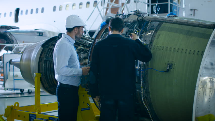 Aircraft Maintenance Mechanic and Chief Engineer Uses Digital Tablet Computer to Analyze, Inspect and Work on Airplane Jet Engine in Hangar. Optimal Functionality, Work, Efficiency and Safety