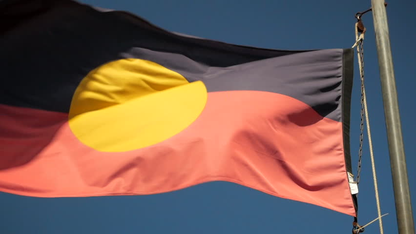 Australian Aboriginal flag flowing in the breeze under a clear blue sky. SLOW MOTION SHOT.