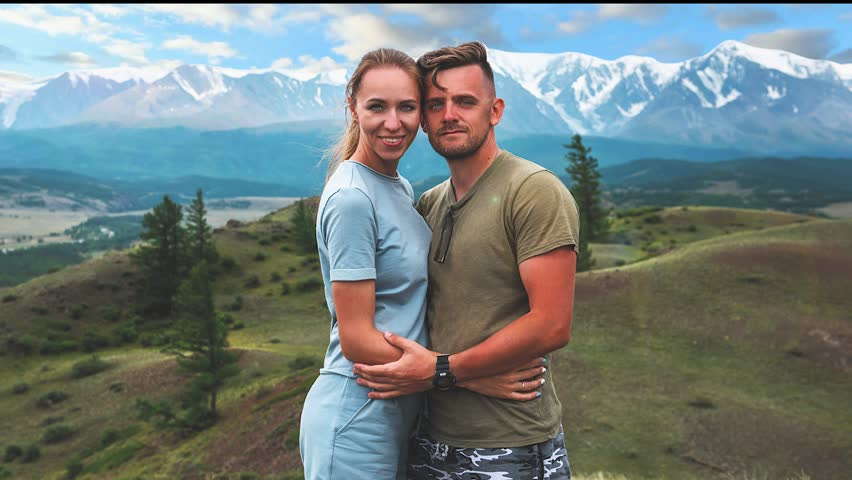 Romantic couple in the mountain, in Altai Mountains. Happy man and woman hug on the background of a mountain glacier, smiling and and look into the camera | Shutterstock HD Video #1027801355