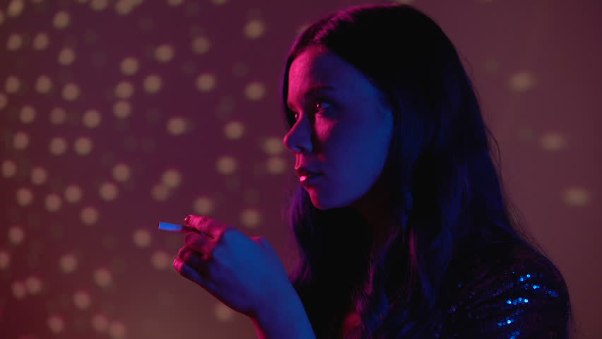Serious young woman smoking cigarette at nightclub party, unhealthy habit | Shutterstock HD Video #1027802216