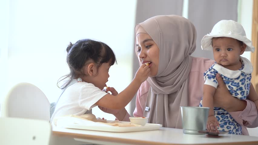 Happy muslim family having a lunch together at home. single mom with two daughter concept. | Shutterstock HD Video #1027807658