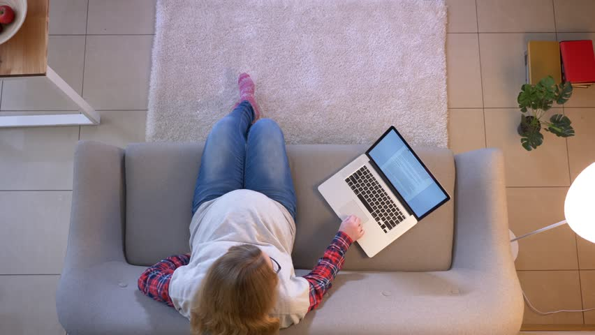 Closeup top shoot of young pregnant female mom working remote using the laptop while sitting on the couch indoors | Shutterstock HD Video #1027819148