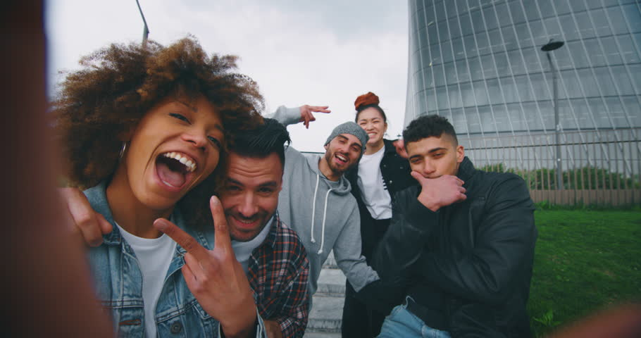 Slow motion of group of young friends of different ethnicities are having fun and making a selfie together with cellular phone in a city center with skyscrapers | Shutterstock HD Video #1027851023