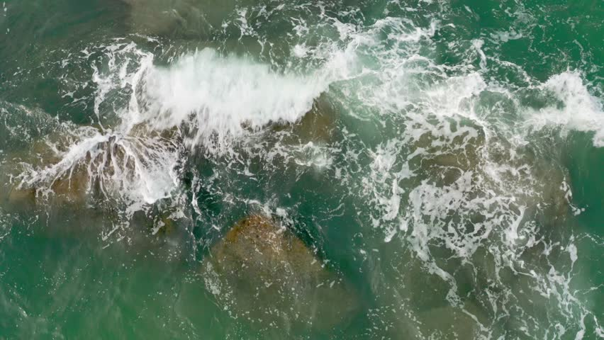 Aerial footage top view the green sea wave and rock stone on island in thailand   | Shutterstock HD Video #1027867445