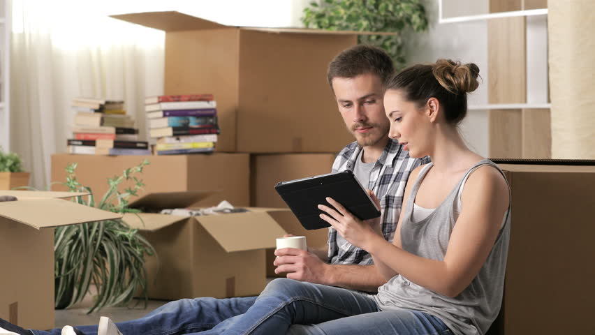 Happy couple moving home using a tablet to plan reforms sitting on the floor Royalty-Free Stock Footage #1027885220