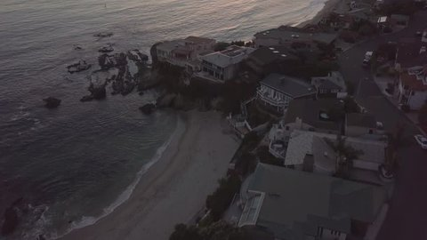 Drone flying backward and then panning up to horizon during sunset in Laguna Beach, California.