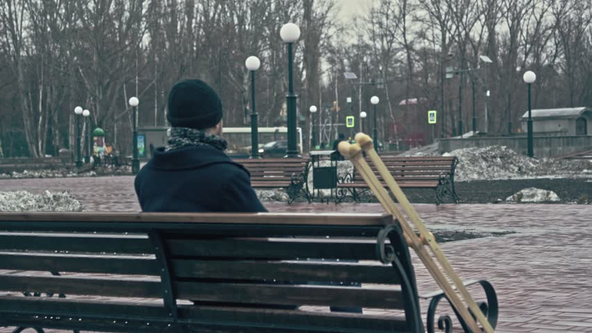 Lone invalid sitting on a bench in the park