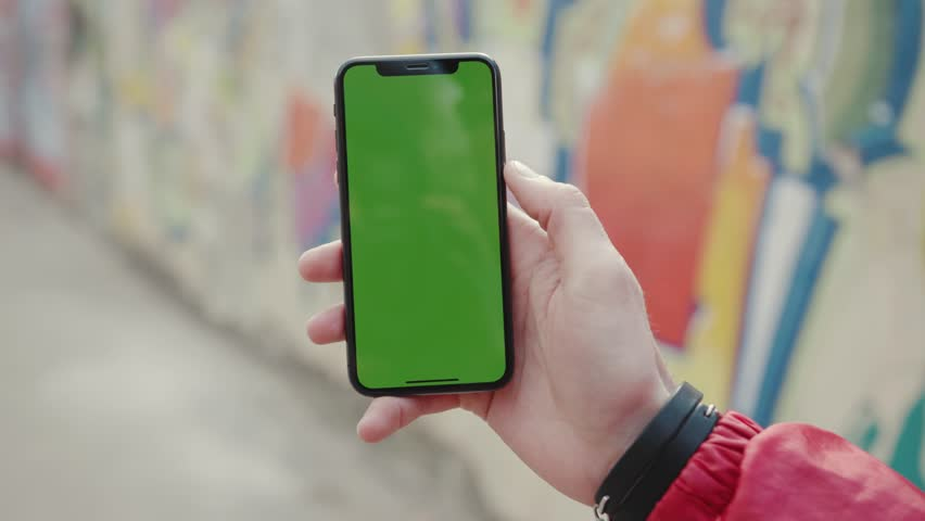 Los Angeles, California 15/03/2019 EDITORIAL: Hands man stand holding and touching phone with green screen vertical background wall city digital internet modern screen smart phone technology sunlight | Shutterstock HD Video #1027898489