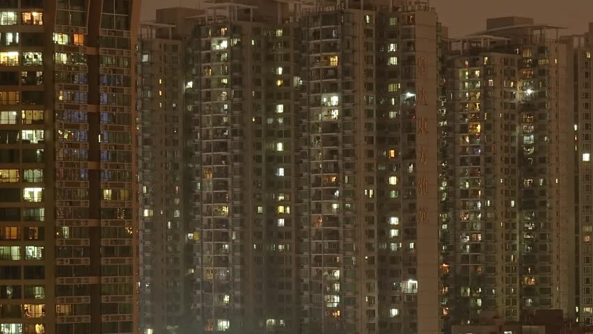 SHENZHEN JAN 2018: Night timelapse of residential windows in Shenzhen. Evening time lapse of apartments with people living in China. Modern life massive apartment buildings in downtown. #1027900004