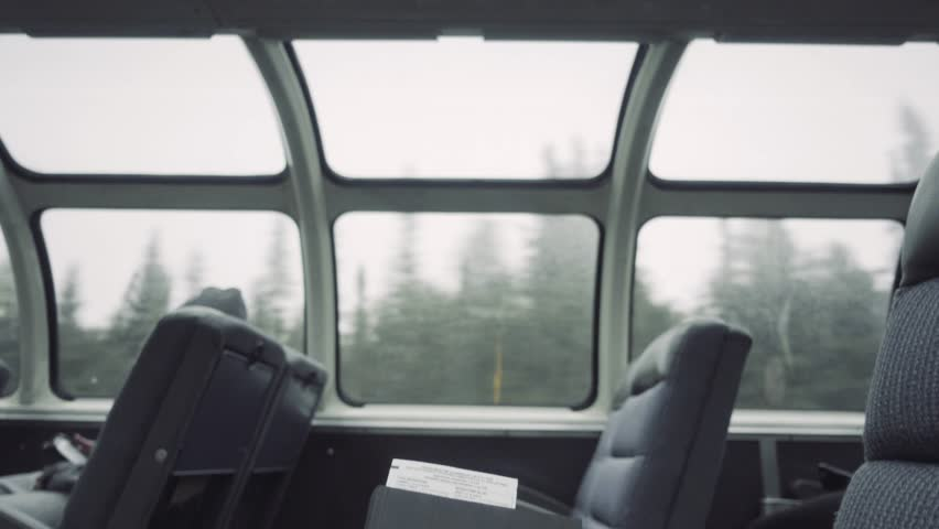 4k interior of a passenger train dome passing through a forest