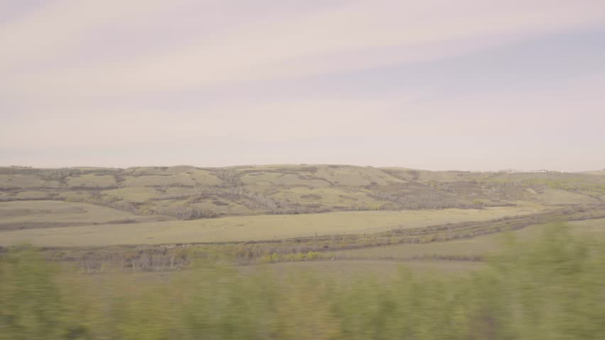 4k Footage passing by hills on a prairie farm from a train