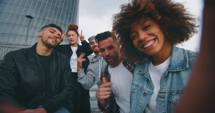 Slow motion of group of young friends of different ethnicities are having fun and making a selfie together with cellular phone in a city center with skyscrapers. | Shutterstock HD Video #1027912154
