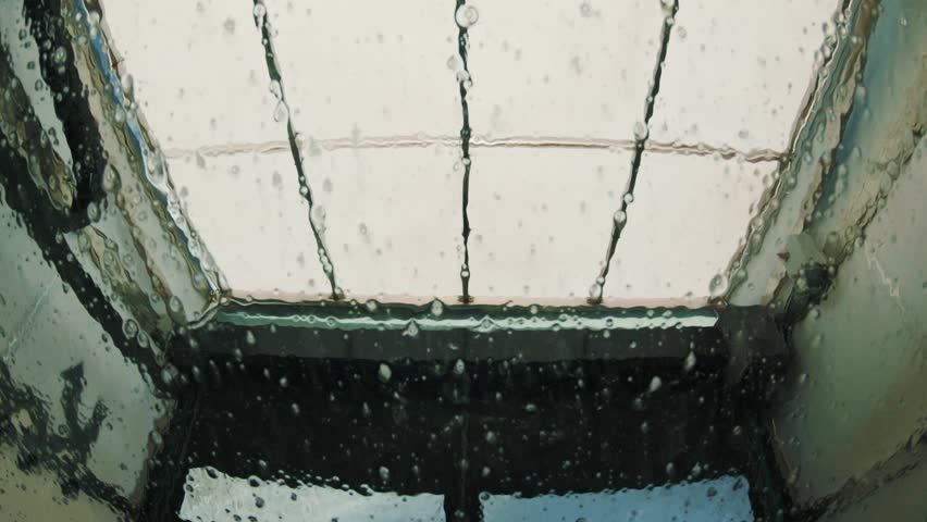 Water streaking down the windshield of a vehicle at the car wash   Shutterstock HD Video #1027922921