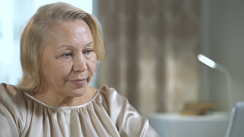 Senior woman of European appearance uses a computer in her home interior. Female portrait #1027927217