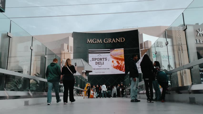 Las Vegas, Nevada / United States - January 6th 2018: Fixed low angle shot of people walking outside an MGM Grand entrance