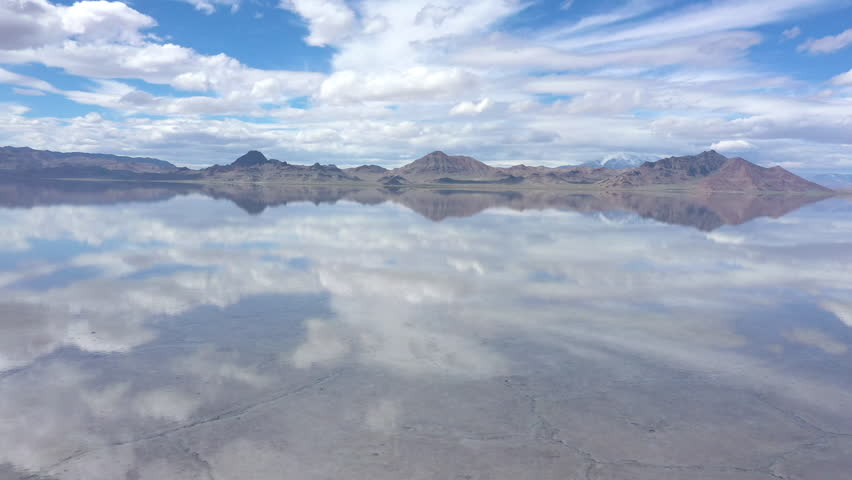 Aerial view flying low over water covering the Bonneville Salt Flats as the sky reflects in the water in Utah.