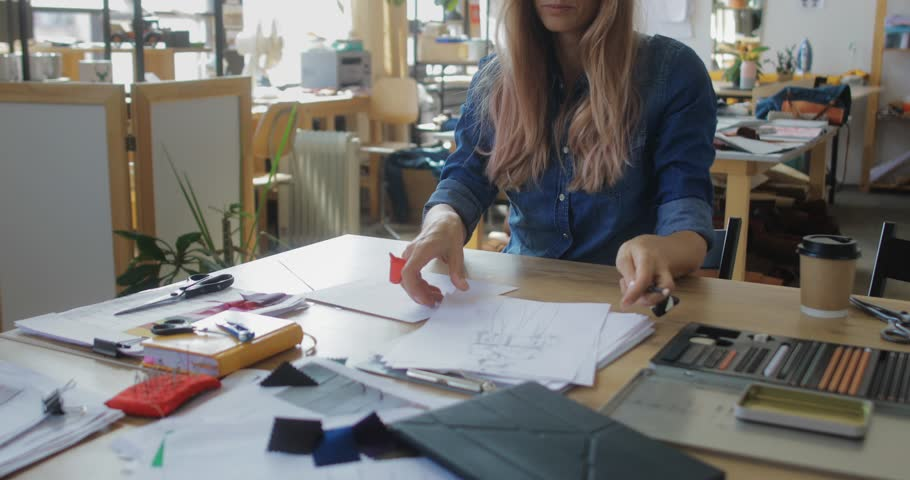 Inspired woman fashion designer creating sketches  at workplace, needlewoman works in studio workshop on new clothes collection ideas, making ethnic cross-stitch embroidery design pattern | Shutterstock HD Video #1027941104