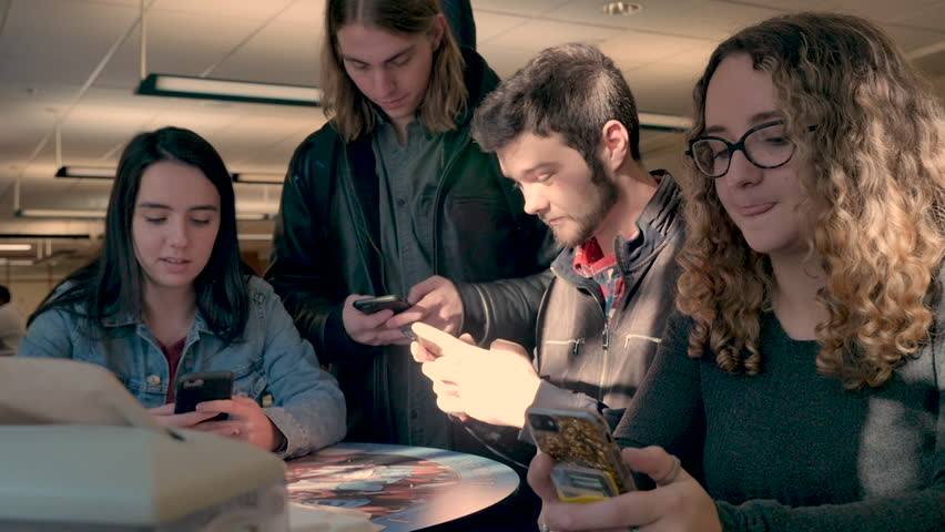 Four college students all using their smart phones and not talking to each other in a cafeteria or public indoor space - slow motion | Shutterstock HD Video #1027951178