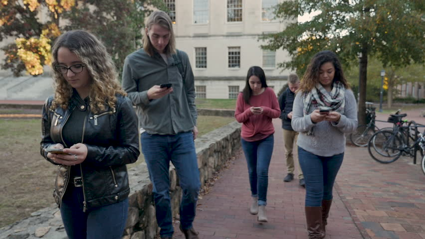 Multi ethnic group of female and male college students walking outdoors on a university campus all on their mobile phones never looking at anything but their smart phones