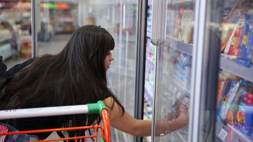 Woman with supermarket shopping cart buying butter. #1027960625